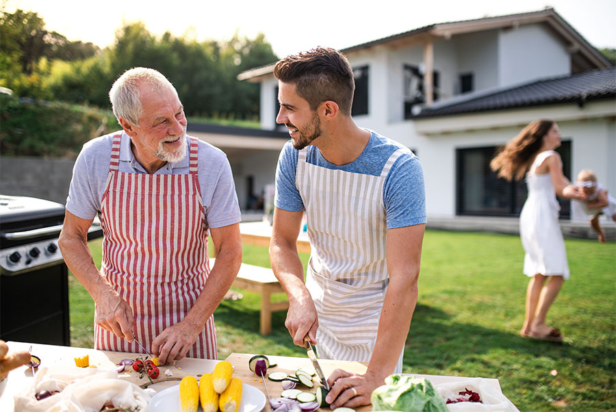 father and grown son in backyard smiling at each other and preparing to barbecue